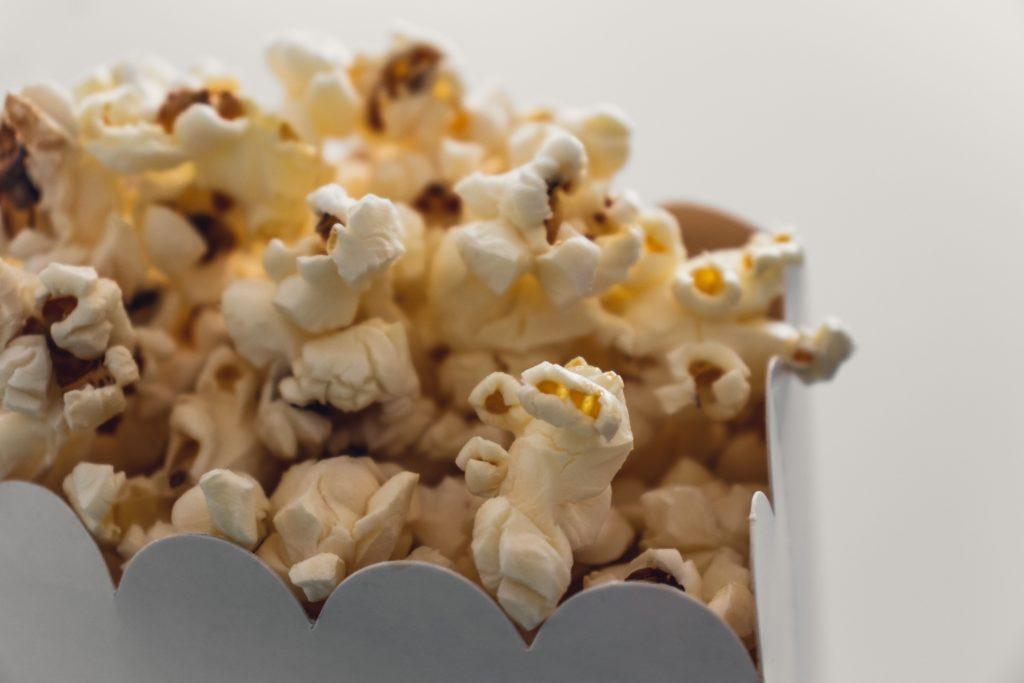 Foto de pipocas para remeter a assistir filmes em casa.