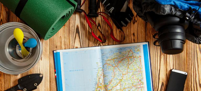 Mapa do mundo em cima de uma mesa com objetos de viagem.